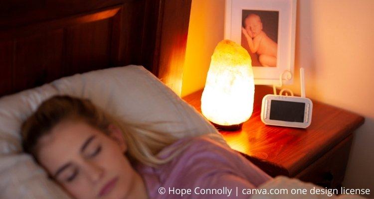 Frau im Bett mit Salzlampe auf Nachttisch